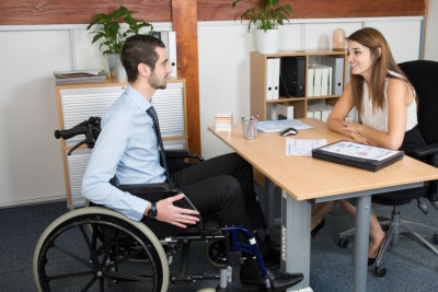 professional consulting an handsome in a wheelchair at his office