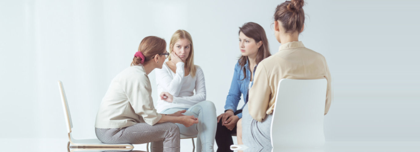 a group of adult woman sitting in a circle during a session with a coaching