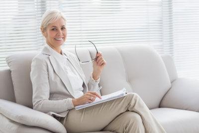 consultants holding eyeglasses sitting on sofa smiling
