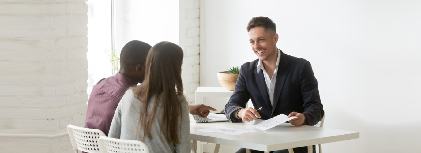 smiling professional business advisor discussing interracial couple about business