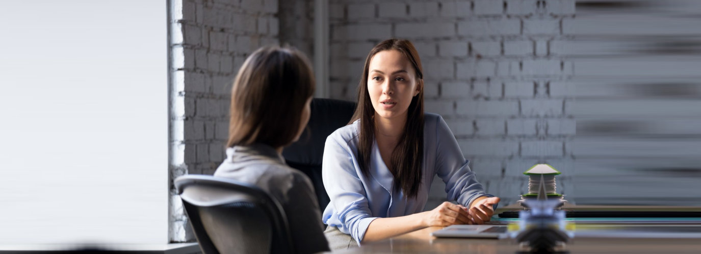 serious professional female advisor consulting an employee at the meeting having business conversation